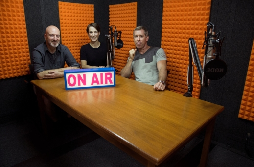 "Colour photo of two men and a woman seated in a recording studio with a big sign reading: ""On Air"".in front of them."