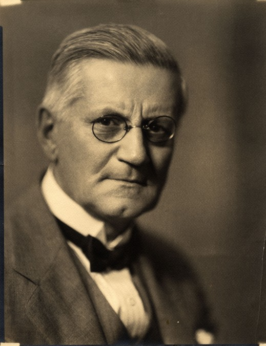 A black-and-white picture of an older man wearing a bow tie and glasses.