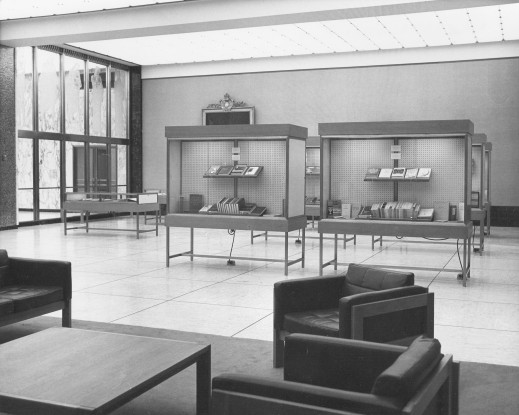A black-and-white photo of a large room with glass displays showing off books.