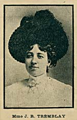 A black-and-white photograph of a young woman wearing a very large hat.