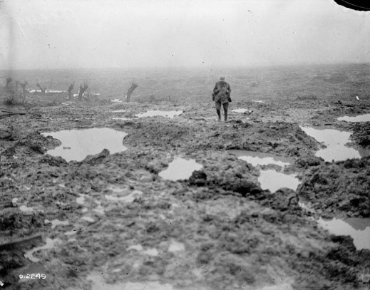 A black-and-white photograph of a soldier walking in a field of mud and puddles.