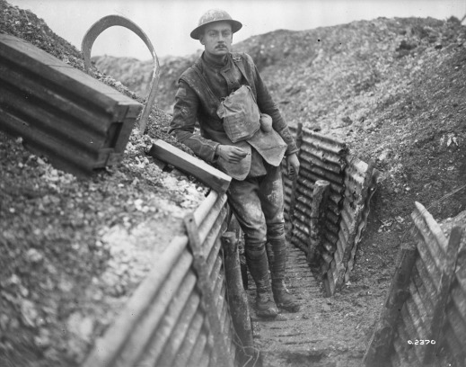 A black-and-white photograph of a muddied soldier leaning on the wall of a trench, smoking a cigarette and looking directly at the photographer.