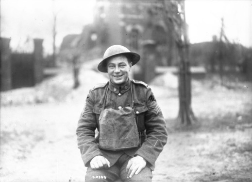 A black-and-white photograph of a smiling soldier wearing a helmet and a leather jerkin.