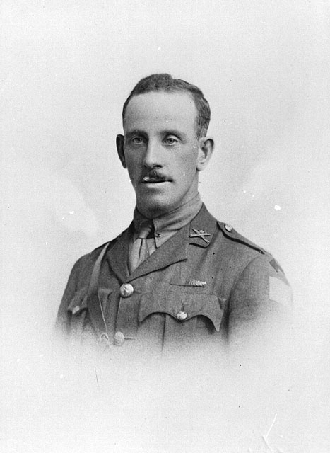 A black-and-white photograph of a uniformed soldier with a small moustache.