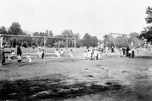 A black-and-white photograph of a park and playground. There are two swing-sets and a teeter-totter. Boys and girls play on the equipment under the supervision of some adults.