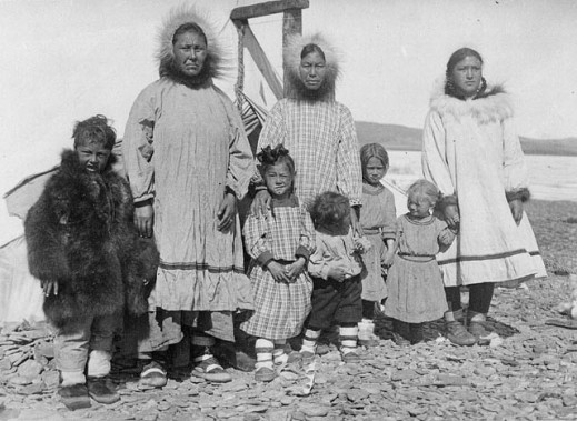 A black-and-white photograph of an unidentified Inuit family of eight people posing for a group portrait. From left to right: boy, woman, girl, woman, boy, girl, girl, woman.