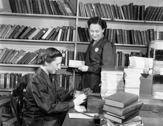 A black-and-white photograph of two women in a library. One is looking through a card catalogue and the other is holding a book and looking at the work of the other.