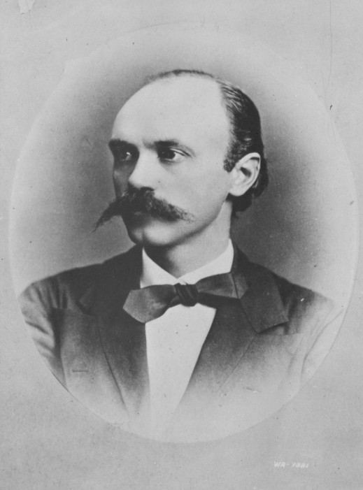 A black-and-white photograph of a man with a prominent mustache, wearing a suit and bow tie. The photo is oval-shaped on a grey matte board.