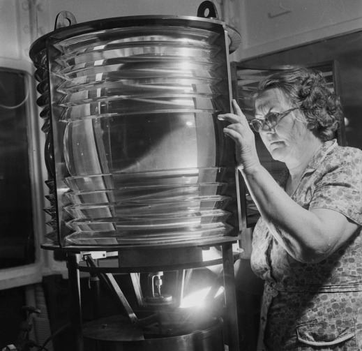 A black-and-white photograph of Eliza Campbell examining a lighthouse lamp.