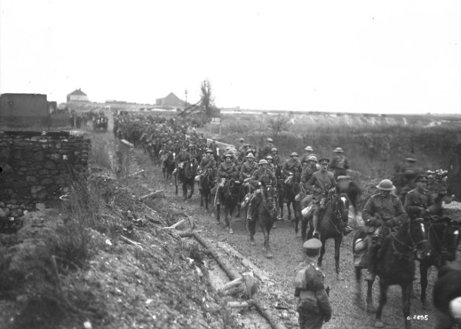 A black-and-white photograph of a line of mounted soldiers riding through a village.