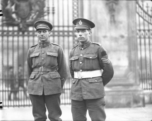 A black-and-white photograph of two soldiers standing in front of an elaborate wrought iron gate.