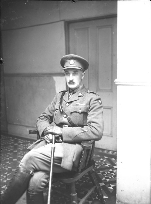 A black-and-white photograph of a seated officer wearing a cap and all the accoutrements of an officer.