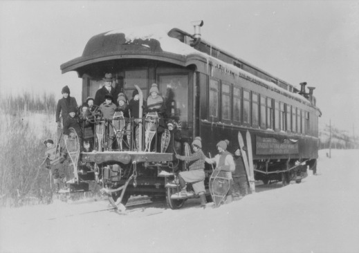 A black-and-white photograph of thirteen children and their teacher posing with their snowshoes at the entry deck of a Canadian National Railway school car.