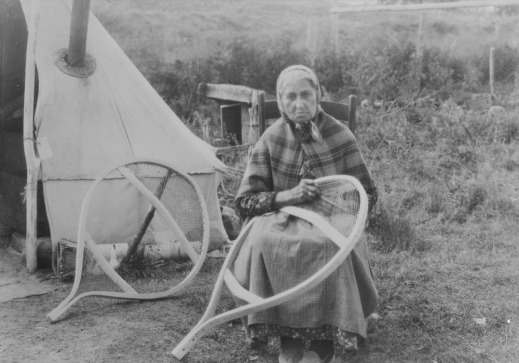 A black-and-white photograph of an unidentified First Nations woman sitting on a chair and working on the webbing of a large round snowshoe.