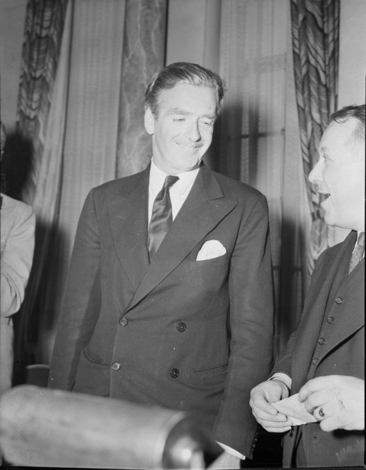 A smiling man speaking with another man against a curtained window with the drapes drawn back. Both men are wearing suits and ties.