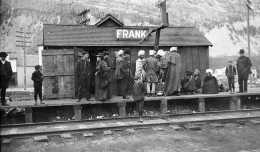 A black-and-white photograph of groups of immigrants on a train platform wearing a variety of clothing from traditional Indian garb with turbans to European styles of clothing. Behind them is the railway station, a small hut with the town's name on the roof. The mountain rises behind the station, and a young boy stands on the tracks.
