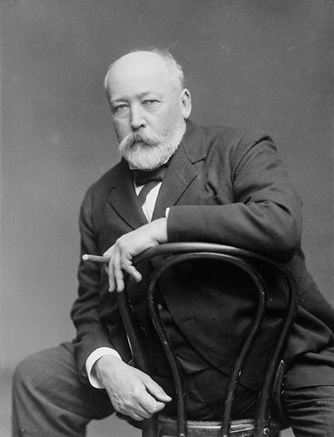 Portrait of a seated man in a suit, straddling a café chair and holding a cigar between two fingers.
