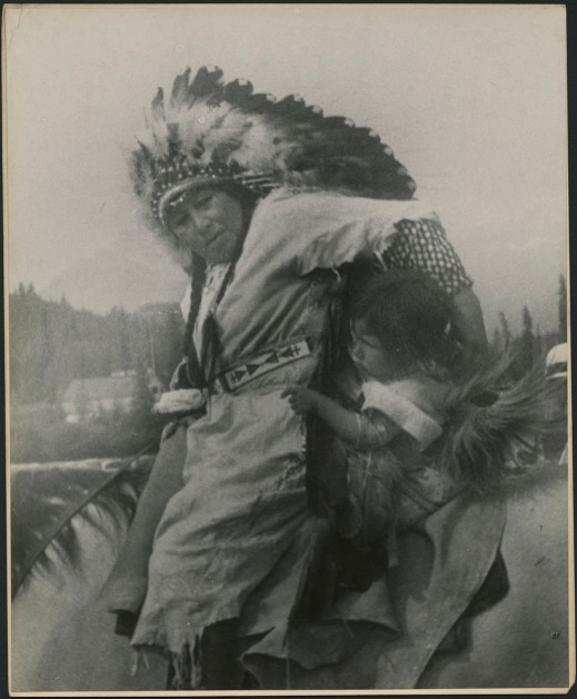 Woman on horseback holding a little girl to her side. The woman is wearing a plain dress with a patterned belt and a feathered headdress over her braided hair.