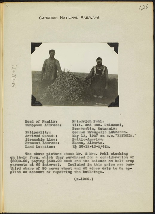 A small black-and-white photograph of a man and woman on either side of a hay bale. A description of the family includes their family name, where they came from, how they arrived, where they live, and a short description of their farm.