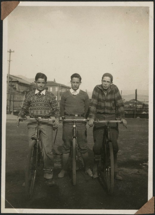 A black-and-white photograph of three boys on bicycles.