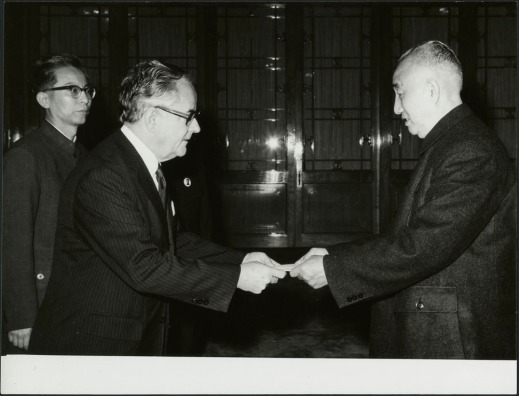 A black-and-white photograph of two men bowing to each other. One of the men is holding a piece of paper and extending it toward the other. In the background, a third man is observing the scene.