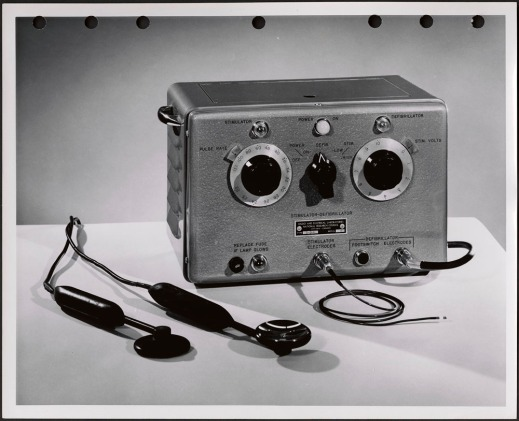 A black-and-white photograph of a small machine with various knobs and dials. Two black wands are connected to the machine by a cord.