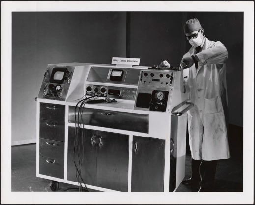 A black-and-white photograph of a man wearing a lab coat, surgical mask and surgical cap. He is looking at his watch and standing next to a large machine with many drawers, knobs and wires. The machine has a sign on it that reads Mobile Cardiac Resuscitator.