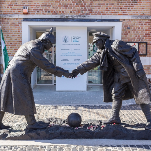Colour photograph of a sculpture of two enemy soldiers leaning over to shake hands over a rugby ball.