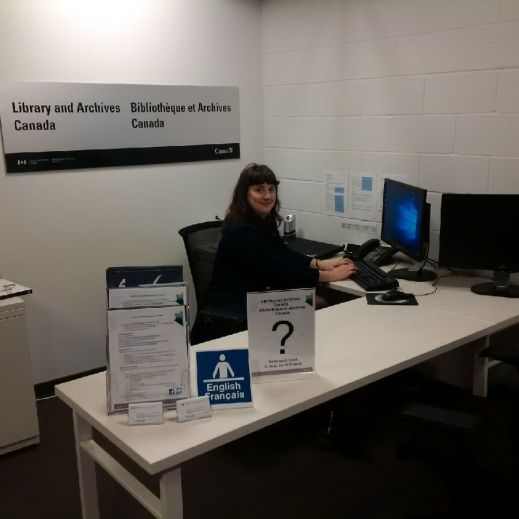 "A colour photograph of a woman sitting at a desk in front of a computer looking at the camera. On the wall behind her is the sign ""Library and Archives Canada – Bibliothèque et Archives Canada."""