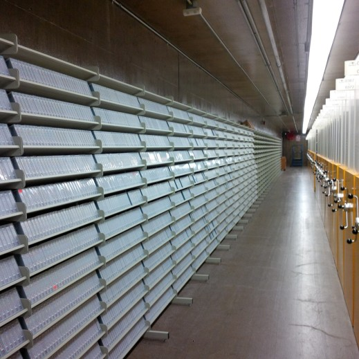 A colour photograph of a long white shelf on the left and high-density storage on the left.