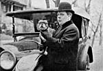 A black-and-white photograph of a man standing in front of a car, holding a small dog and wearing a Bowler hat.