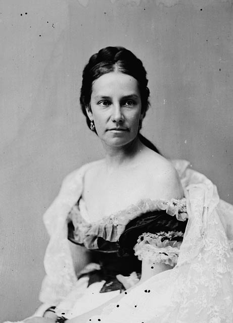 A black-and-white photograph of a woman who is looking slightly off to the left. Her hair is parted down the center, tied back away from her face, and she is wearing an off-the-shoulder evening dress.