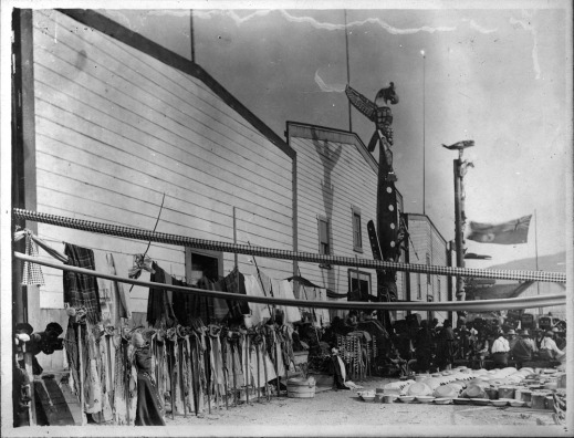 A black-and-white photograph of a streetscape with potlatch participants and items to be given away.