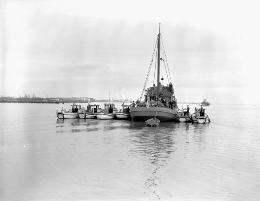 A black-and-white photograph of six Japanese-Canadian fishing boats confiscated three days after Pearl Harbor and tied to a larger vessel.