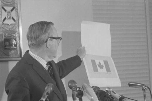 A black-and-white photograph of a man holding an illustration of the Canadian flag.