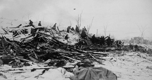 A black-and-white photograph showing a line of people digging through the rubble of destroyed buildings.
