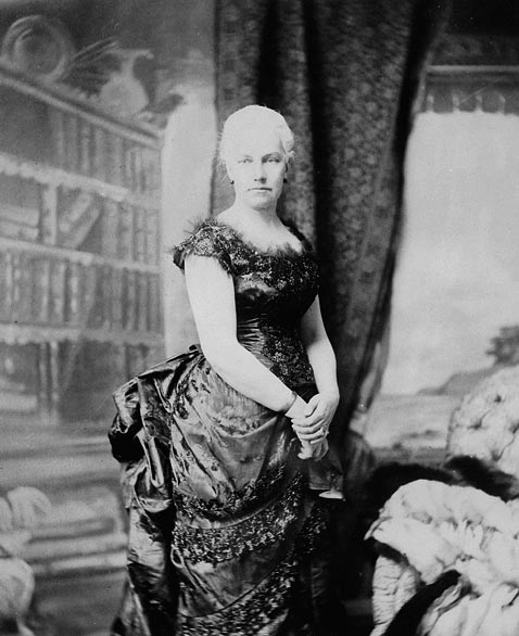 A black-and-white photograph of a woman wearing a long, dark-coloured dress. Her hair is white and is pulled back into a bun.