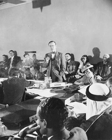 A black-and-white photograph of a man standing up and addressing a room of people.