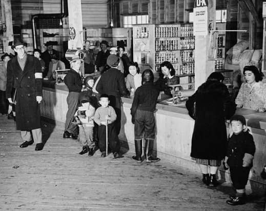 A black-and-white photograph of Japanese-Canadian families buying supplies in an internment camp store in Slocan City, British Columbia, observed by a Caucasian man wearing an armband.