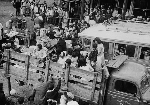 A black-and-white photograph of many Japanese-Canadian families at a staging area being loaded on the backs of trucks for relocation to an internment camp in the British Columbia interior.