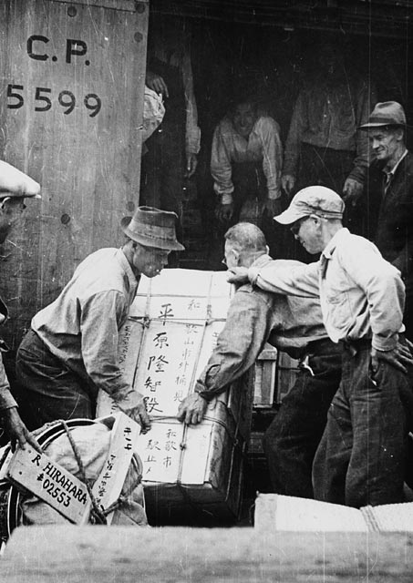 black-and-white photograph of three Japanese-Canadian men loading a rail car destined for an internment camp in the British Columbia interior.