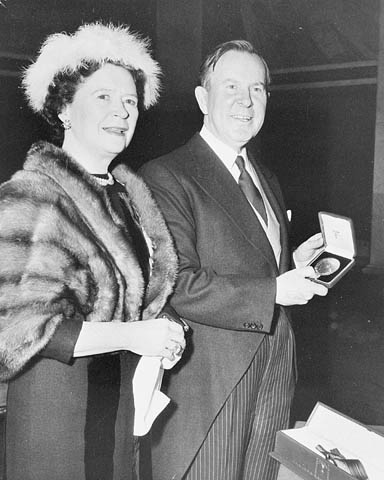 A black-and-white photograph of a formally dressed couple. The man is holding a box with a medallion.