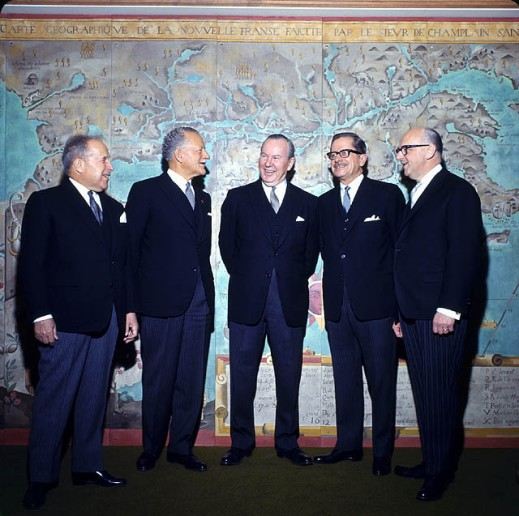 A colour photograph of a group of men standing in front of an enlarged map of New France.