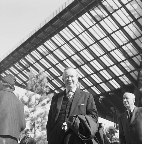 A black-and-white photo of man standing under an interesting architectural building.