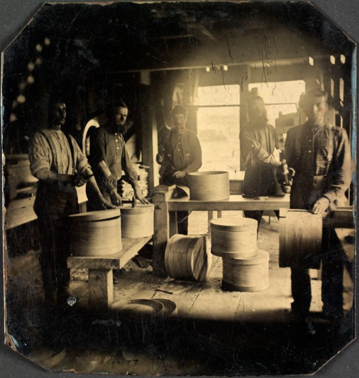 A black-and-white photograph of five men assembling wooden boxes inside a mill.