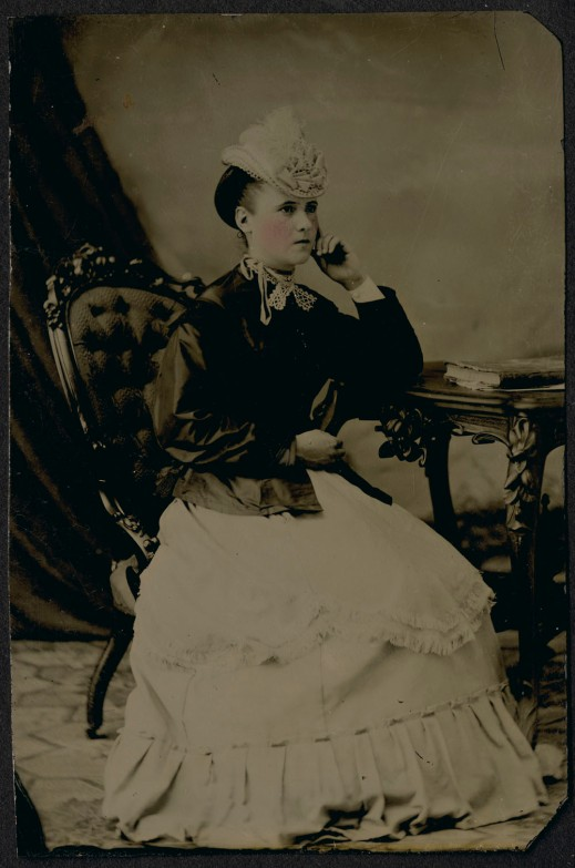 A hand-tinted, black-and-white portrait of a seated woman.