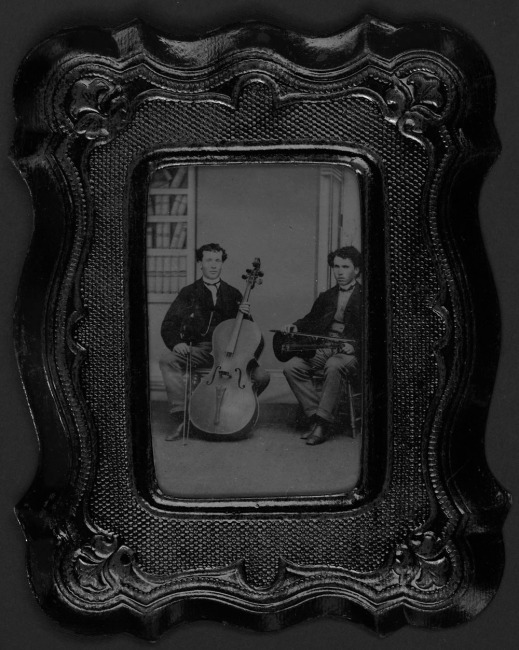 A black-and-white portrait of two young men seated. One is holding a violin and the other is holding a cello.