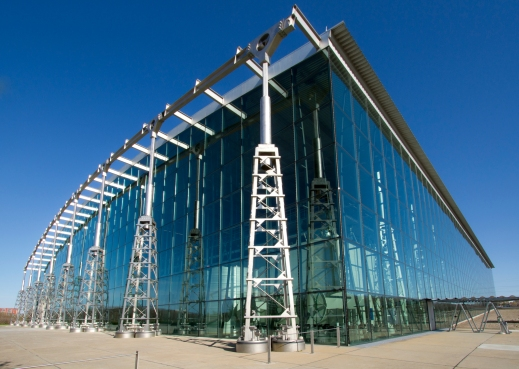 A colour photograph of a large modern building made out of glass with metal pillars.