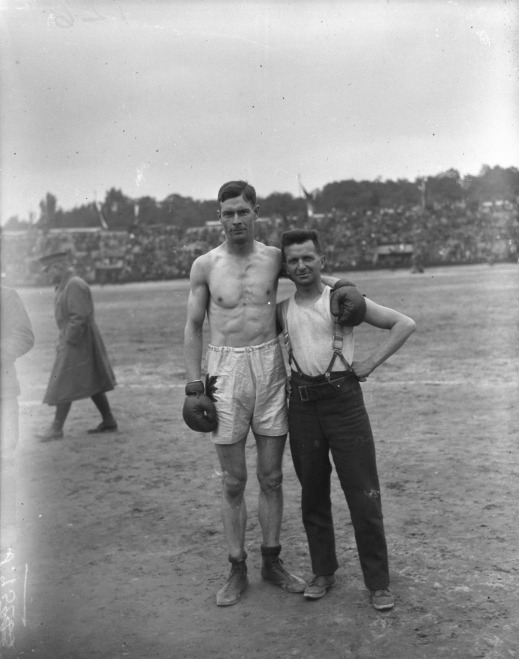 A black-and-white photograph of middleweight boxer Edwin A. Harris (Canada) in his trunks and gloves, posing with another soldier.