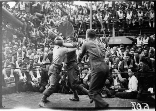 A black-and-white photograph of two boxers fighting on the deck of the SS Justicia, surrounded by the ship's complement of soldiers.